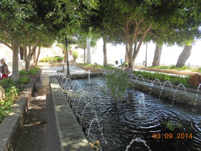 Mijas Springbrunnen unter Schatten spendenen Bäumen
